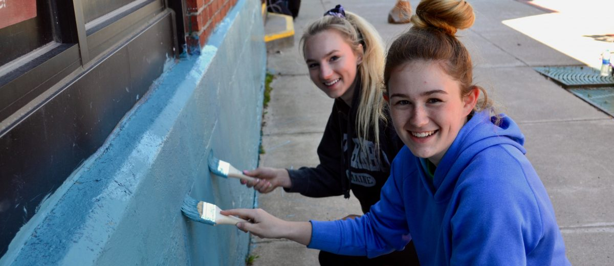 two teen girls smiling painting a wall blue