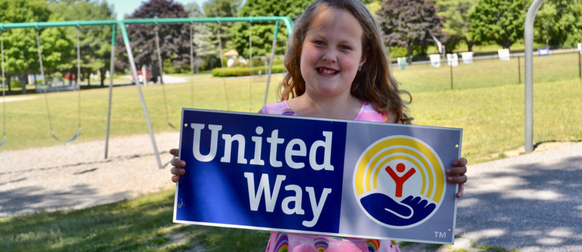 girl holding united way sign in front of playground