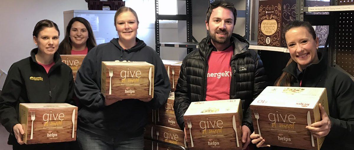 volunteers holding give a meal boxes